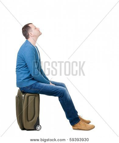 back view man sitting on suitcase. waiting at the station. backside view person.  Rear view people collection. Isolated over white background. guy with travel bag on wheels looking at something at top
