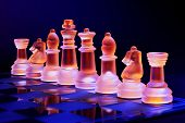 picture of chessboard  - Glass chess on a chessboard lit by a colorful blue and orange light and placed on a glass chessboard - JPG