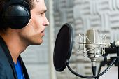 picture of singer  - Young male singer or musician with microphone and headphone for audio recording in the Studio - JPG