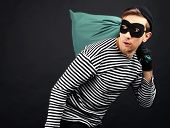 stock photo of plunder  - Thief with bag isolated on black - JPG