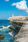 stock photo of malecon  - The castle of El Morro in Havana and the famous  wall of Malecon with white puffy clouds on a blue sky - JPG