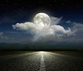 stock photo of moon silhouette  - Dramatic sky over an asphalt road - JPG