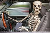 picture of seatbelt  - A skeleton behind the wheel of an SUV distracted by his cell phone. He is also not wearing a seatbelt.