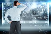 Thinking businessman with hand on head against math equation background