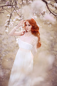 stock photo of fairy tail  - Beautiful woman in the flowering park near the apple - JPG