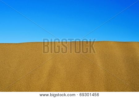view of the crest of a sand dune against the blue sky