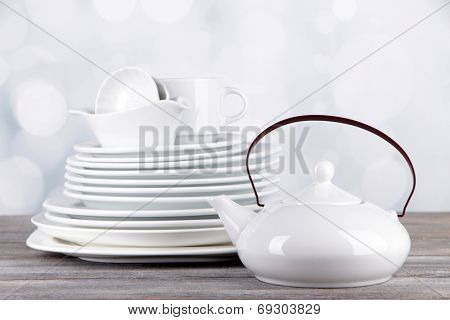 White crockery and kitchen utensils, on wooden table, on light background