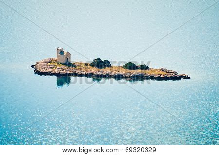 Small Isolated Island With A Lighthouse In The Adriatic Sea In Croatia