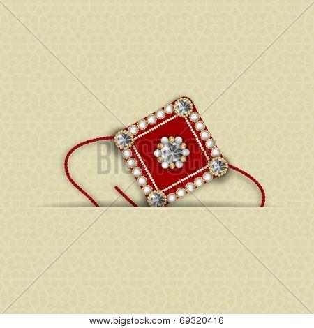 Beautiful maroon rakhi decorated with diamonds on brown background for Hindu community festival Raksha Bandhan celebrations.