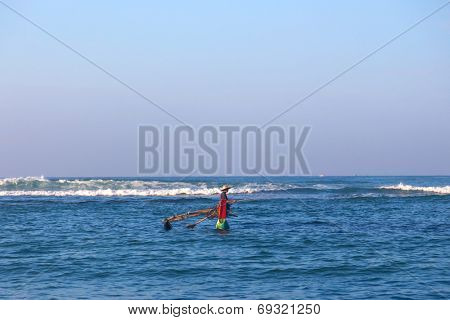 UNAWATUNA, SRI LANKA - MARCH 6, 2014: Fisherman in boat at Dalawella Beach. These traditional boats enable fishermen to surf the waves without getting washed away.