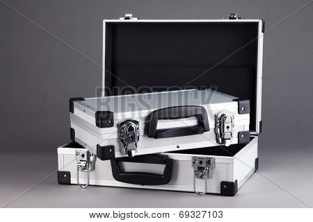 Silvery suitcases on grey background
