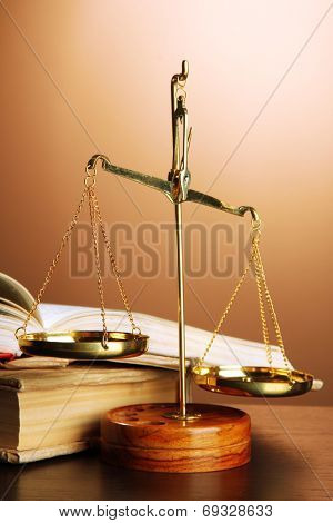 Gold scales of justice and books on brown background