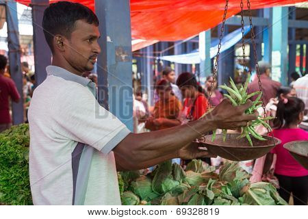 HIKKADUWA, SRI LANKA - MARCH 9, 2014: Local street vendor weighing beans. The Sunday market is great way to see Hikkaduwa's local life come alive along with fresh produce and local delicacy