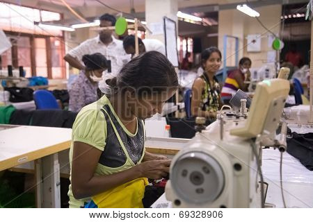 COLOMBO, SRI LANKA - MARCH 12, 2014: Local women working on sewing machine in apparel industry. The manufacture and export of textile products is one of the biggest industries in Sri Lanka.