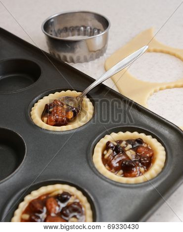 Using Teaspoon To Fill Pastry Cases With Mincemeat