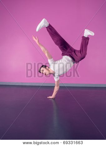 Cool break dancer doing handstand on one hand in the dance studio