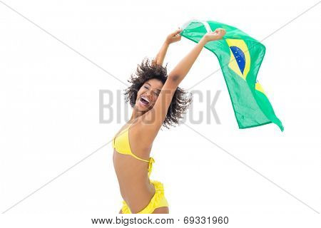 Fit girl in yellow bikini holding brazil flag laughing at camera on white background