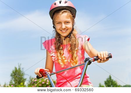 Cute young girl holding bicycle