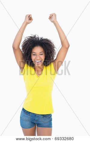 Pretty girl in yellow tshirt cheering at camera on white background
