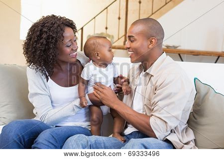 Happy young parents spending time with baby on the couch at home in the living room