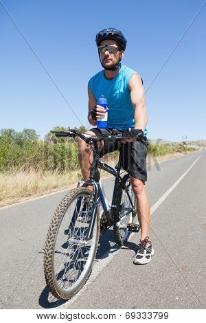 Handsome cyclist taking a break on his bike on a sunny day