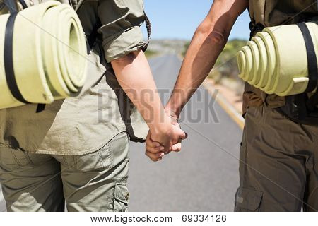 Hitch hiking couple standing holding hands on the road on a sunny day