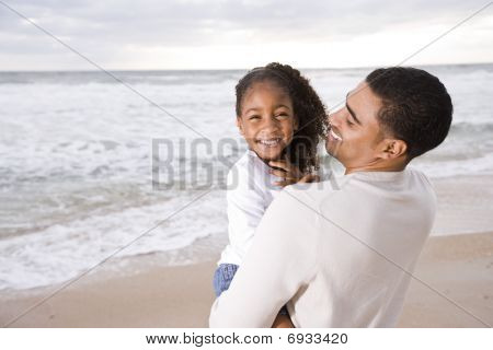 African-American dad hold little girl at beach
