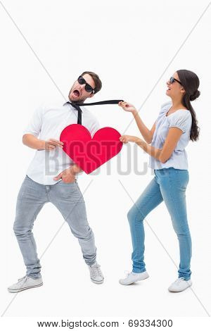 Brunette pulling her boyfriend by the tie on white background