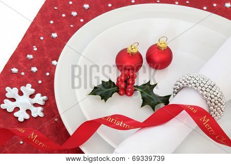Christmas dinner place setting with white plate, red ribbon and baubles, holly and serviette with silver ring on  table cloth.