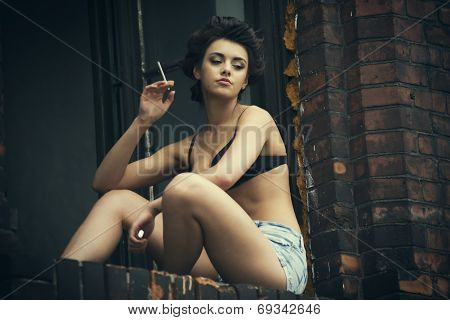 Beauty Retro Woman Smoking Cigarette And Sitting On Windowsill
