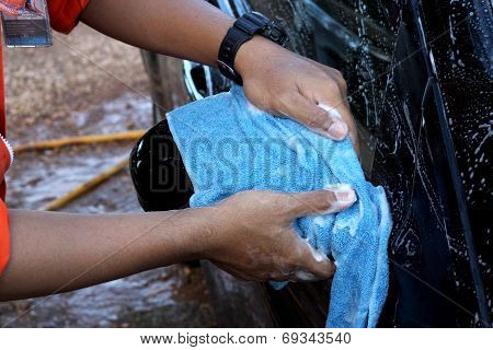 cleaning black car by hand