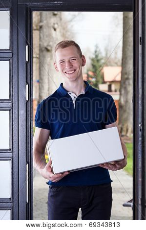 Courier Standing With Box In House Door
