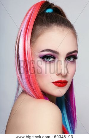 Portrait of young beautiful girl with colorful ponytail