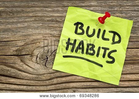 build habits reminder - self-development concept - handwriting on a green sticky note against grained and knotted wood board
