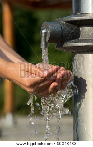 Catching Fresh and Cool Water from a Spring with Hands