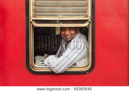 HIKKADUWA, SRI LANKA - FEBRUARY 22, 2014: Smiling passenger framed in train window. No trains are air-conditioned so passengers just open the windows.