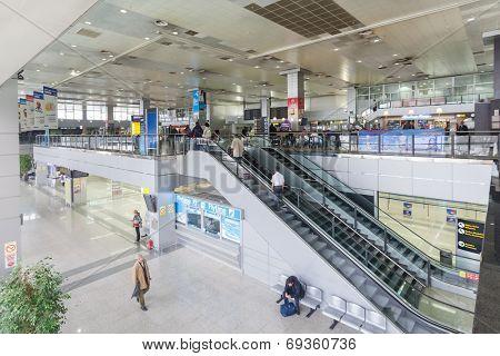 BELGRADE, SERBIA - FEBRUARY 18, 2014: Passengers  at escalator and hall at Belgrade airport Nikola Tesla, the fastest growing major airport in Europe.