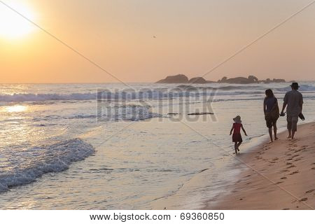 HIKKADUWA, SRI LANKA - FEBRUARY 24, 2014: Family walking on sandy beach at sunset. Hikkaduwa is very popular place for family vacationers.