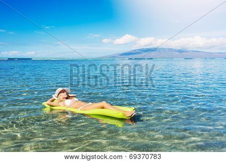 Sexy woman in bikini floating on inflatable pool mattress in the ocean relaxing
