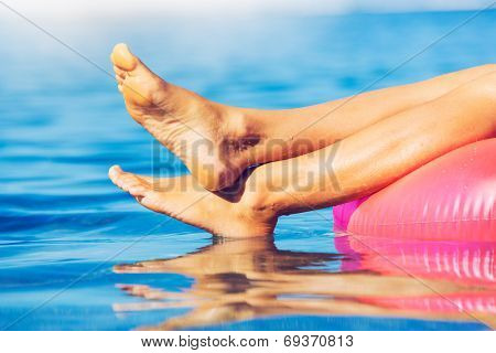 Sexy young woman in bikini relaxing floating in the ocean, close up view of legs and feet
