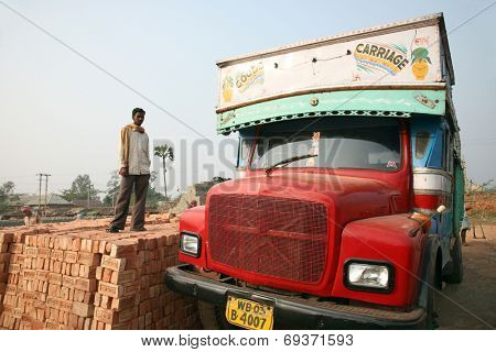 SARBERIA,INDIA, JANUARY 16: Brick field workers carrying complete finish brick from the kiln, and loaded it onto a truck on January 16, 2009 in Sarberia, West Bengal, India.