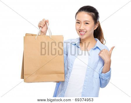 Woman with shopping bag thumb up