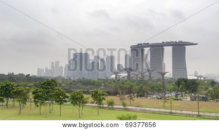 SINGAPORE - 31 DEC, 2013: Marina Bay Sands hotel - most expensive building in the world on city's skyline panorama. Famous Gardens By The Bay in the front of composition