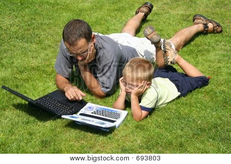 Boy And His Father Working On Laptops On Green Grass