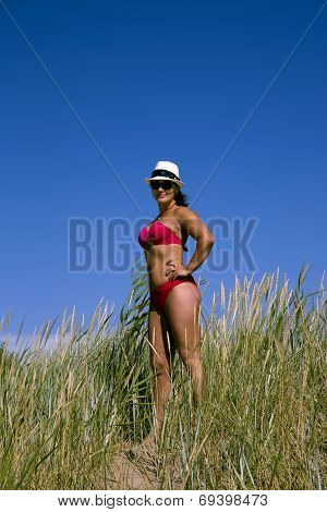 A beautiful girl in a swimming suit stands in a high grass