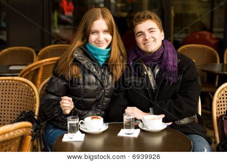 Happy Young Couple In A Parisian Street Cafe