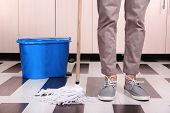 stock photo of cleanliness  - Young man cleaning floor in room - JPG
