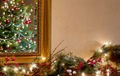pic of mantle  - A traditionally decorated Christmas tree is reflected in a mirror over a hearth with a trail of red berries pine boughs and twinkling lights - JPG