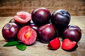 picture of strawberry plant  - plums on a dark wood background - JPG