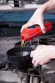 Постер, плакат: Man Changing Motor Oil